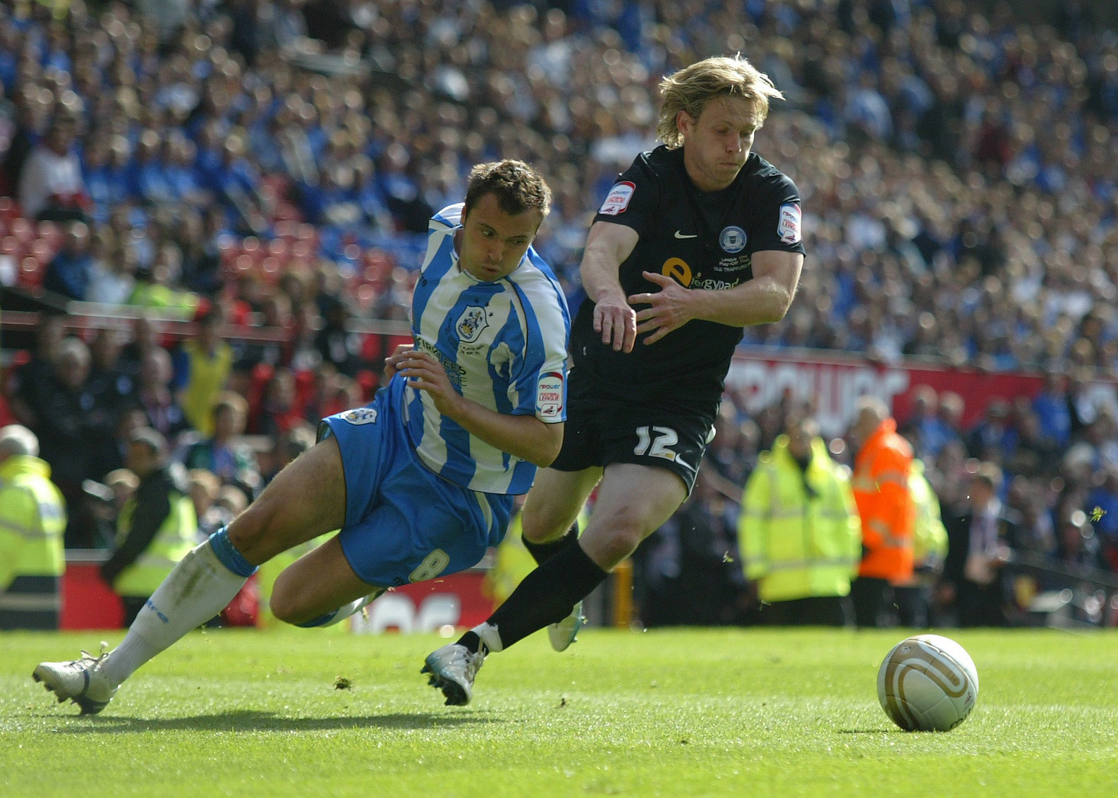 Craig Mackail-Smith gets the ball off Antony Kay of Huddersfield Town