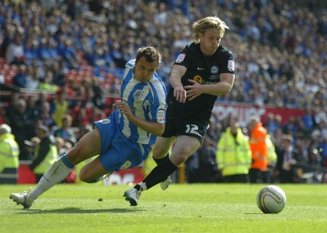 Craig Mackail-Smith gets the ball off Antony Kay of Huddersfield Town