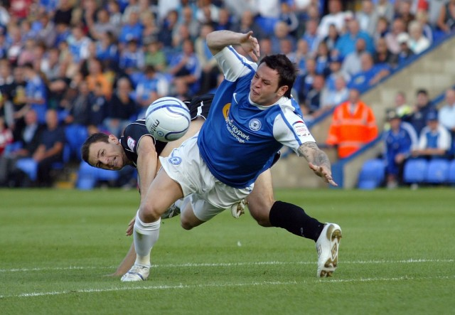 Lee Tomlin brought down for a penalty by Tommy Smith
