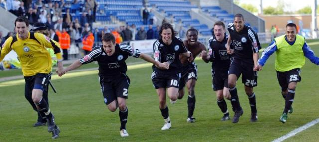 Players celebrating promotion at Colchester