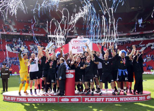 The Peterborough United squad and management celebrate winning promotion as captain Grant McCann lifts the Play-Off Final winners