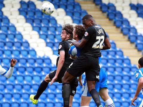 Cristian Burgess and Ricardo Santos challenge for a header v Colchester