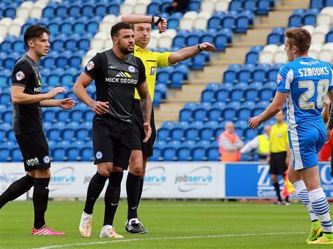 Kyle Vassell in front of an animated referee Carl Boyeson v Colchester