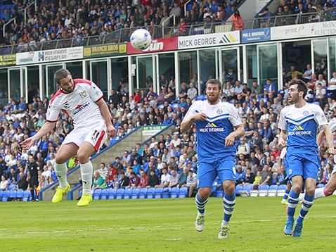 Michael Bostwick and Michael Smith watch MK Dons Will Grigg head goalwards