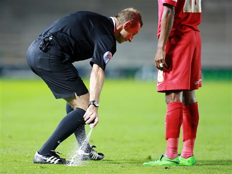 Referee Keith Hill uses the vanishing spray in front of the wall