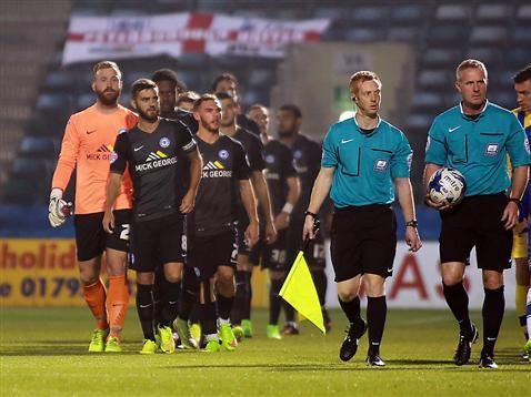 Referee Mark Heywood leading Posh out v Gillingham