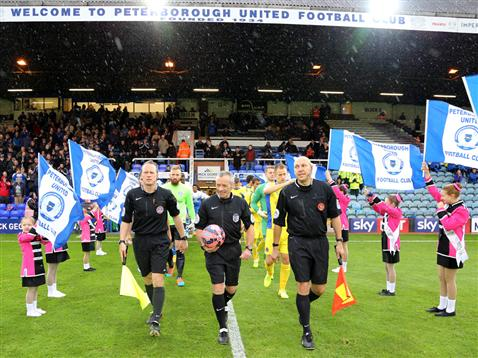 Referee Scott Mathieson leads the teams out at London Road