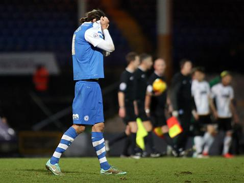Christian Burgess hides his head in shame after the defeat by Port Vale