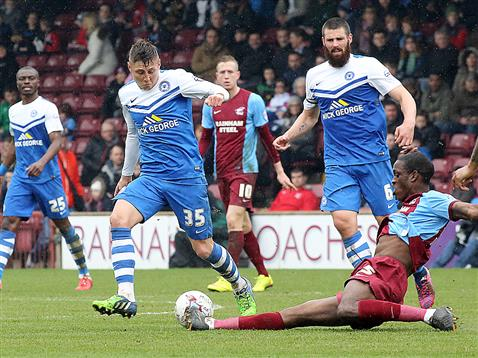 Harry Beautyman watched by Michael Bostwick and Gaby Zakuani v Scunthorpe