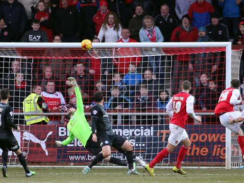 Scott Loach dives but the ball hits the crossbar by Fleetwood