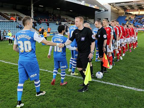 Match officials during the handshake between Posh and Crewe