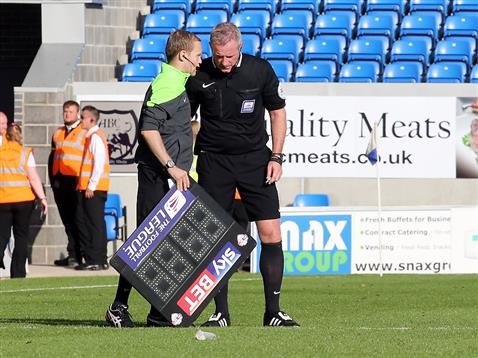 Fourth official informs referee Mark Heywood to send off Jermaine Anderson for throwing his water bottle into the crowd