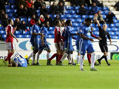 Harry Beautyman crumpled on the floor while referee Nick Kinseley shows Barnsleys Long the red card