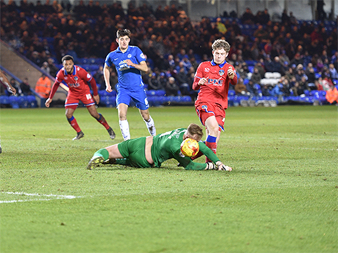 Ben Alnwick misses the ball but brings an Oldham player down