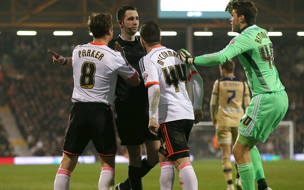 Referee Chris Kavanagh surrounded by angry Fulham players after sending off Konstantinos Stafylidis