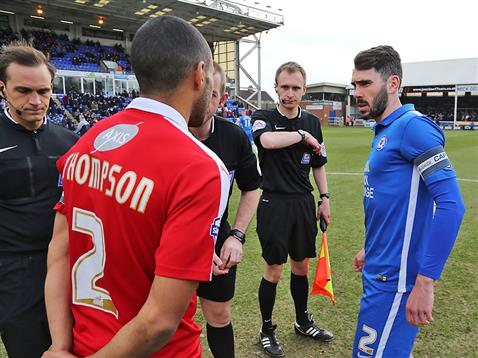 Referee Darren Handley partly hidden by Swindon captain and Michael Smith