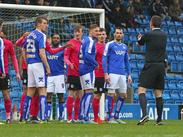 Referee David Coote warns Chesterfield and Posh players at a corner