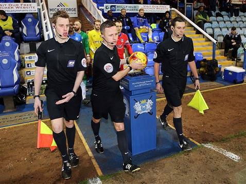 Referee David Webb leads out Posh and Oldham