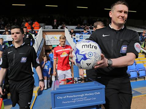 Referee Lee Collins leads out Posh and Crewe