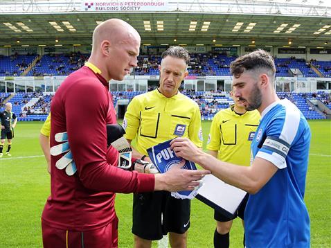 Referee Darren Deadman watches Michael Smith exchange penants with Norwich captain John Ruddy