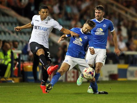 Gwion Edwards and Michael Smith cant stop a cross from Swansea