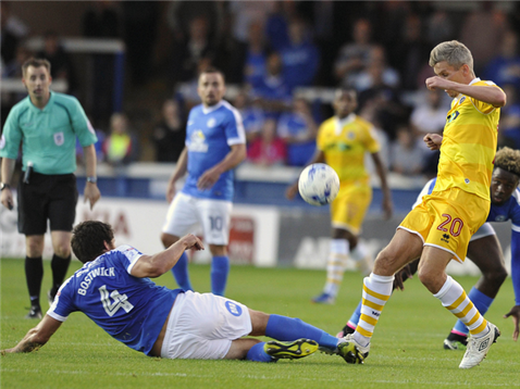 Referee Ross Joyce watches Michael Bostwick tackle Steve Morison of Millwall