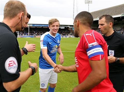 Referee Tim Robinson watches Chris Forrester shake hands with Swindon captain