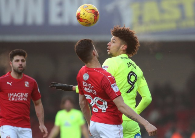 Posh striker Lee Angol in an aerial duel at Swindon. Photo: Joe Dent/theposh.com.
